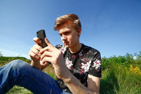 wireless telephone: Teenager texting on his smartphone outside in summer