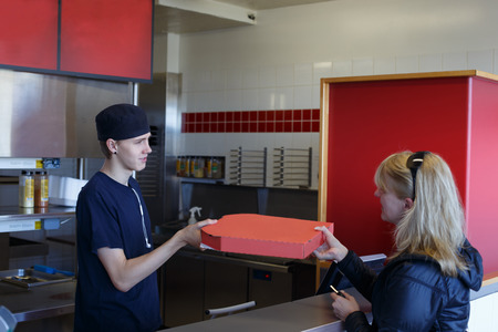 Young man handing over a pizza in a fast food restaurant