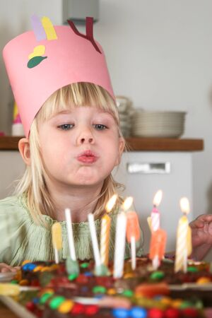 party pastries: Young girl blowing out candles on her birthday cake Stock Photo