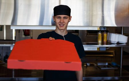 handing over: Young man handing over a pizza in a fast food restaurant