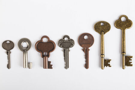 key ideas: Row of old fashioned keys isolated on white Stock Photo
