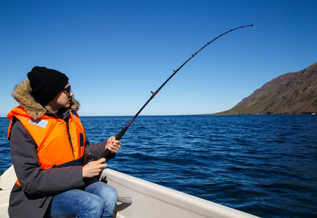 sea fishing: Young man salt water fishing, fish on the line