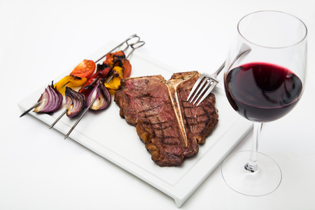 t bone: T bone steak on a white plate with grilled vegetable and glass of red wine shot on white