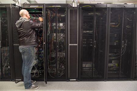 server data: Network administrator working on cabling in a server cabinet