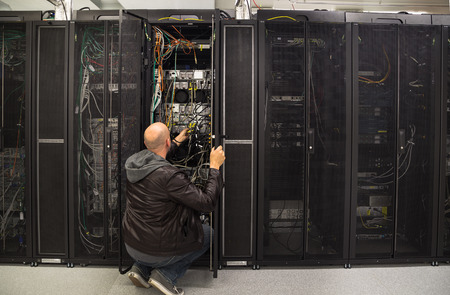 routed: Network administrator working on some problem in a server room Stock Photo