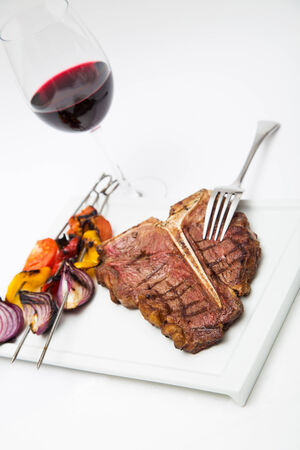 charbroiled: charbroiled steak with red wine and grilled vegetables on a plate,isolated on white, horizontal format Stock Photo
