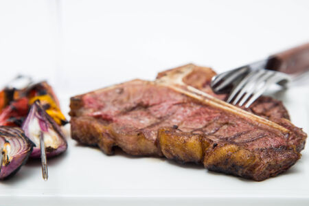 charbroiled: T-bone steak on a white plate with some grilled vegetables, prepared at a restaurant, isolated on white