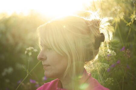 backlit: Profile shot of a backlit woman in a meadow, soft focus and lens flare.