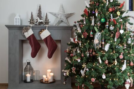 christmas stockings: cropped shot of a candle fireplace with stuffed christmas stockings hanging over it, Lighted candles and decorated christmas tree Stock Photo