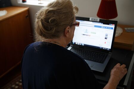 person computer: Older woman using her computer to browse the internet and keep in touch Stock Photo