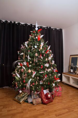 night before christmas: christmas tree with christmas presents under it in a real living room Stock Photo