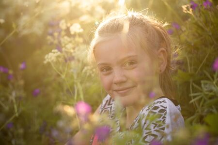 backlit: Young girl smiling at camera surrounded by wildflowers in a meadow during summer, backlit by the afternoon sun. soft focus Stock Photo