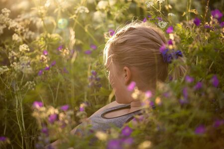 looking away from camera: Teenage girl enjoying summer lying in a field of wildflowers, looking away from camera