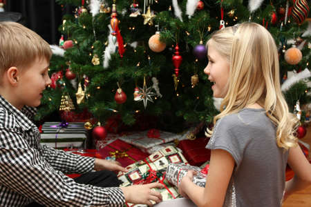 christmas time: Two young children smiling and laughing with christmas presents under the tree Stock Photo