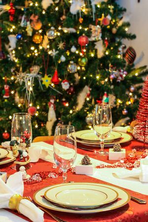 Table set for christmas dinner, decorated christmas tree in the background  photo