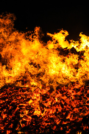 pyre: Close up shot of a burning fire set against a black background, red hot embers in the bottom