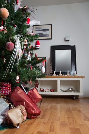 christmas tree decoration: Cropped shot of presents under a decorated christmas tree in a real living room Stock Photo