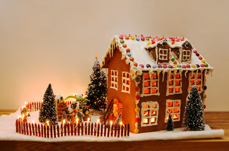 Homemade gingerbread house decorated with whitle glazing and candy and lighted with small lights