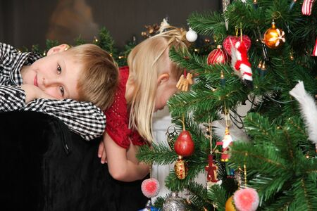 Young children waiting by the christmastree until they can open the presents photo