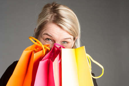 shopping trip: Woman looking at camer from behind shopping bags after a shopping trip, copy space Stock Photo