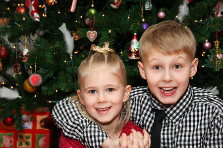 Young boy and young girl happy and looking at camera on christmas day photo