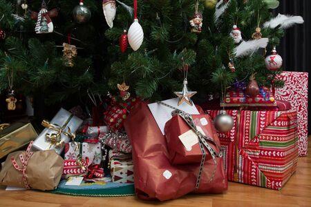 christmas tree presents: close up shot of christmas presents under a christmas tree