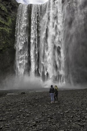 Tourists looking at a big waterfall named Skogafoss in southern Iceland photo