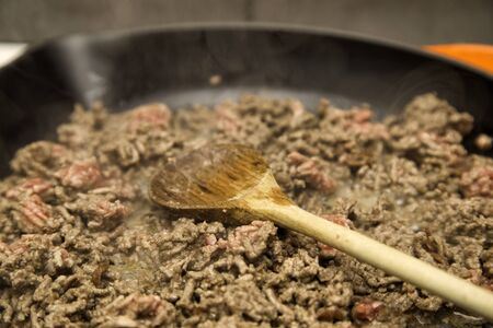 fryed: Minced meat being fryed in a pan, wooden spatula lying in the pan and steam coming of the meat.