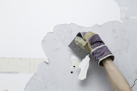 person scraping white paint of concrete wall during a home remodeling project Stock Photo