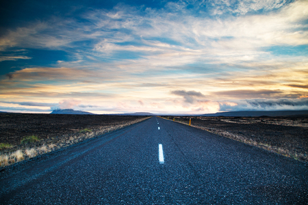 Road leading into the distance under a dramatic sky Stock Photo