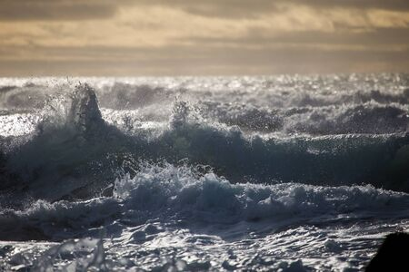 foaming: waves crashing on land after a storm, dramatic skies and foaming water