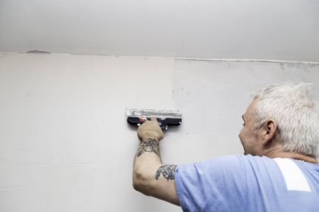 Painter spackling a concrete wall in preperation before painting it