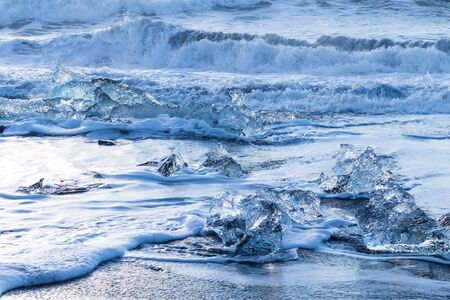 chunks of glacial ice melting in the waves on a beach in Iceland