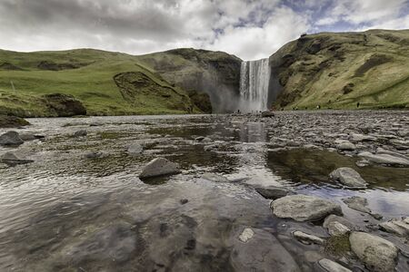 Skógá and Skógafoss waterfall, shot from downriver in early icelandic spring. Stock Photo