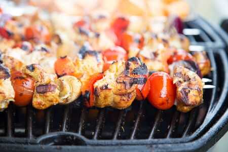 Barbecue skewers being grilled on a bright summer day, close up with shallow focus
