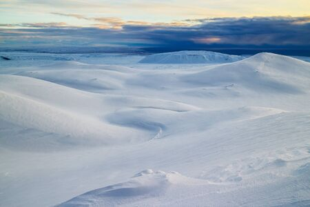 expanse: Winter landscape with snow covered mountains in Iceland, dramatic skies in the background.
