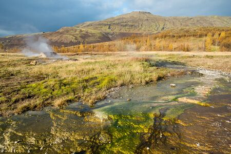 The Geysir area in Haukadalur Iceland shot in autumn, steam coming up of the ground with coloroful mineral deposits in foreground Reklamní fotografie
