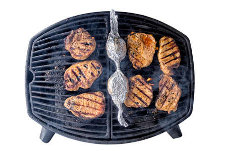 Porkchops on a barbecue grill isolated on white with clipping path, flames and smoke coming up from it