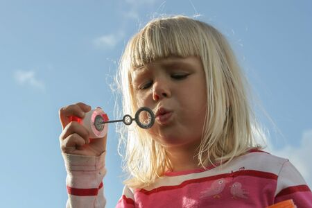 A cute small girl blowing soap bubbles photo