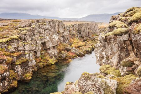 A Fissure in Thingvellir national park in Iceland, shot in autumn with full fall colors evident. Overcast sky