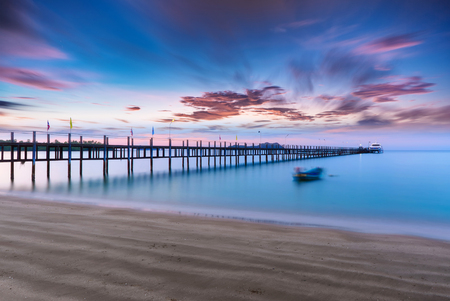 sea scenery: Low light long exposure scenery of a sea with woode bridge,with motion blur effects on surface of water and sky. Stock Photo