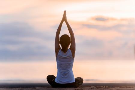 Jeune femme pratiquant le yoga sur la plage au coucher du soleil. Banque d'images - 74557560