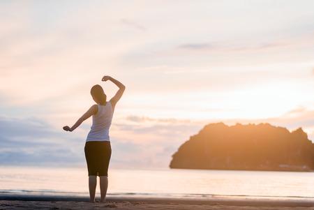 Femme détendue respirant de l'air frais sur le lever du soleil de la plage. Banque d'images - 74557593