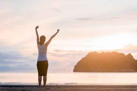 Femme détendue respirant de l'air frais sur le lever du soleil de la plage. Banque d'images - 74557594