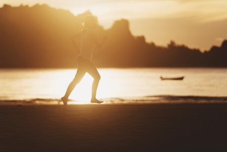 image of Woman running on the beach at sunrise.