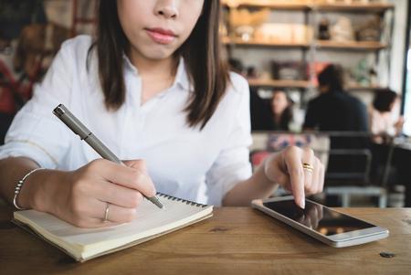 Jeune femme écrivant dans le cahier tout en utilisant le smartphone. Banque d'images - 77213934