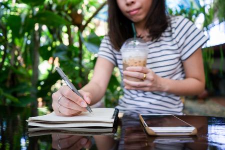 Jeune femme utilisant un smartphone avec une tasse à thé glacée et un cahier. Banque d'images - 77186747