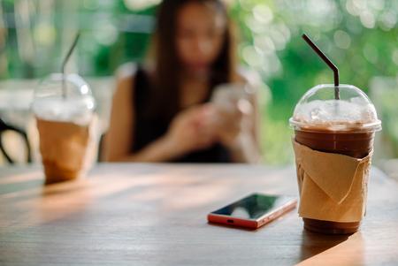 Jeune femme utilisant un smartphone dans un café. Banque d'images - 78966579