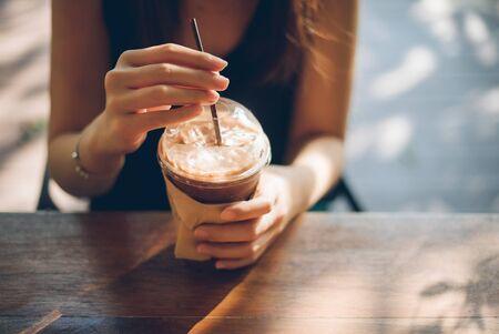 Main de femme tenant une tasse de café sur une vieille table en bois. Banque d'images - 79056015