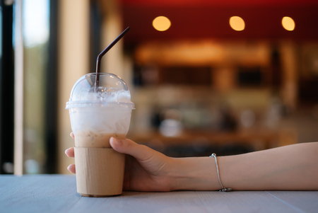 Hand of woman holding coffee cup on white table.